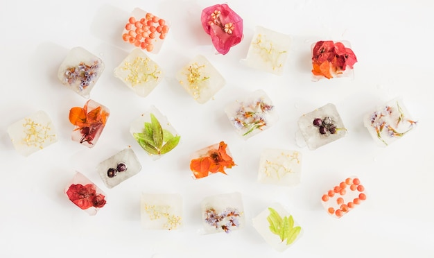 Ice cubes with bright flowers on white background