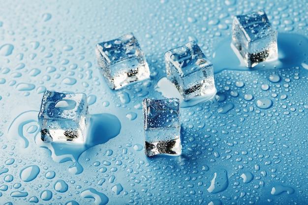 青いテーブル、上面図に溶けた水の滴と角氷。蒸し暑い中の鮮度。冷たい飲み物