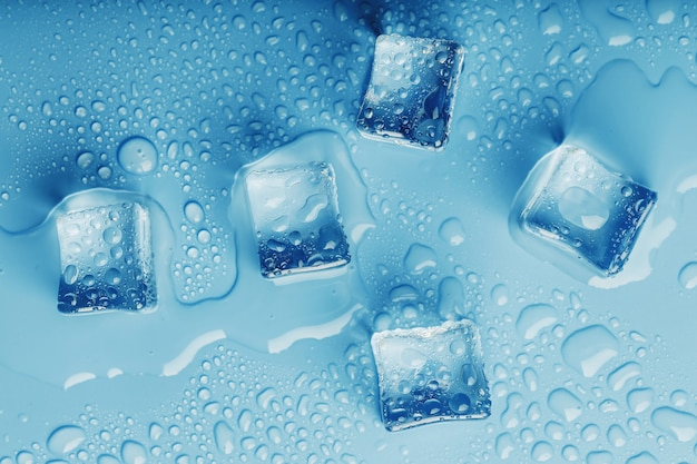 Кубики льда с каплями талой воды на синем фоне, вид сверху.