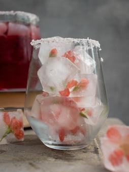 Кубики льда с цветами в стакане