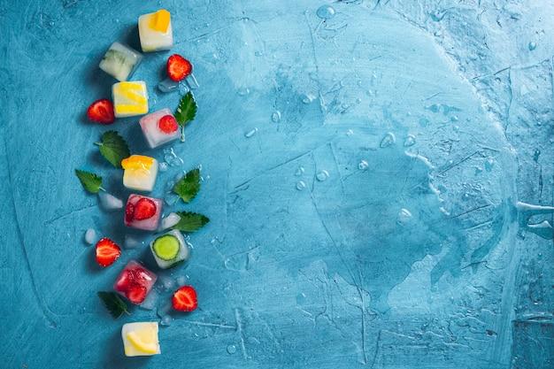 フルーツとミントの葉と新鮮なフルーツの石の青い背景に壊れた氷のアイスキューブ。ミント、ストロベリー、チェリー、レモン、オレンジ。フラット横たわっていた、トップビュー
