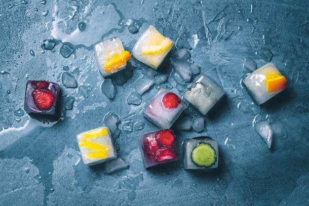 青い石の表面に果物と砕いた氷のアイスキューブ。ミント、ストロベリー、チェリー、レモン、オレンジ。フラットレイ、トップビュー