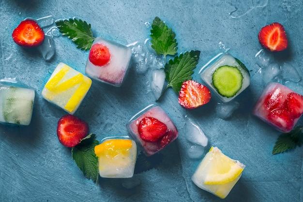 ミントの葉と新鮮な果物と石の青い表面に果物と壊れた氷のアイスキューブ。ミント、イチゴ、チェリー、レモン、オレンジ。フラット横たわっていた、トップビュー