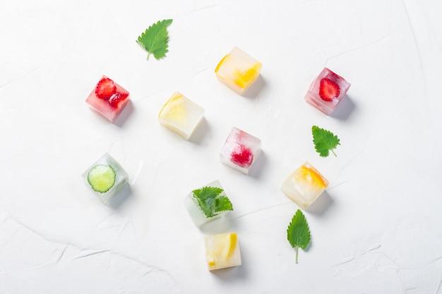 과일과 민트와 얼음 조각 흰 돌 배경에 나뭇잎. 과일 얼음 개념, 갈증 해소, 여름. 평평한 평면도, 평면도
