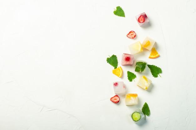 白い石の背景にフルーツとミントのアイスキューブを残します。フルーツアイスのコンセプト、喉の渇きを癒す、夏。フラット横たわっていた、トップビュー