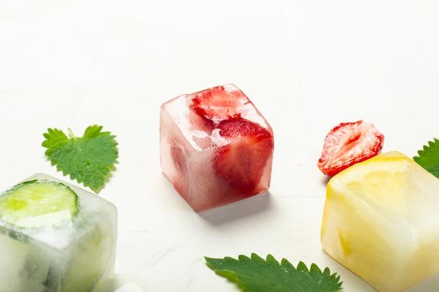 白い石の背景にフルーツとミントのアイスキューブを残します。フルーツアイスのコンセプト、喉の渇きを癒す、夏