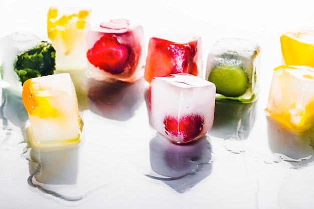 Ice cubes with fruit on a bright white surface. the concept of hot summer, dessert, ice cream. flat lay, top view