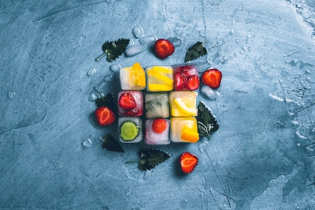 Ice cubes with fruit and broken ice on a stone blue background with mint leaves and fresh fruit. cube shape. mint, strawberry, cherry, lemon, orange. flat lay, top view