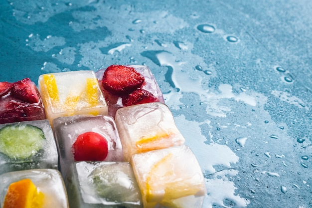 Ice cubes with fruit on a stone blue surface. the shape of the square. mint, strawberry, cherry, lemon, orange. flat lay, top view