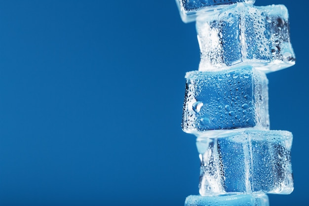Ice cubes with water drops tower in a row on a blue background.