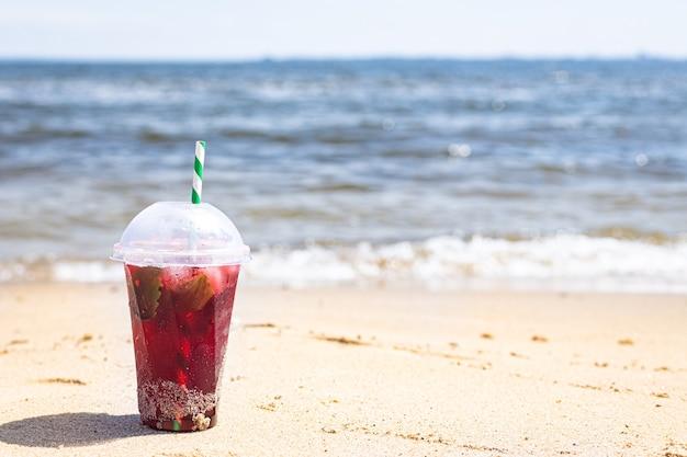 Ice drink red lemonade soda on the beach cherry or strawberry fresh juice sea coast shore summer surf wave