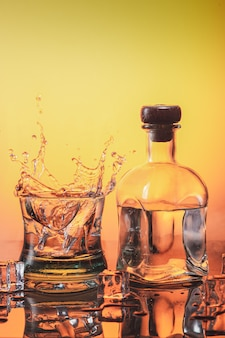 Ice falling on a glass of whisky making splash and a bottle of liqueur on orange base with ices