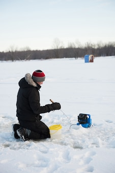 Pescatore sul ghiaccio pesca nel paesaggio innevato
