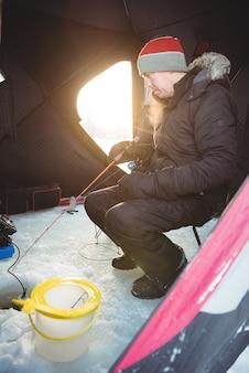 Pescatore sul ghiaccio che pesca stando seduti