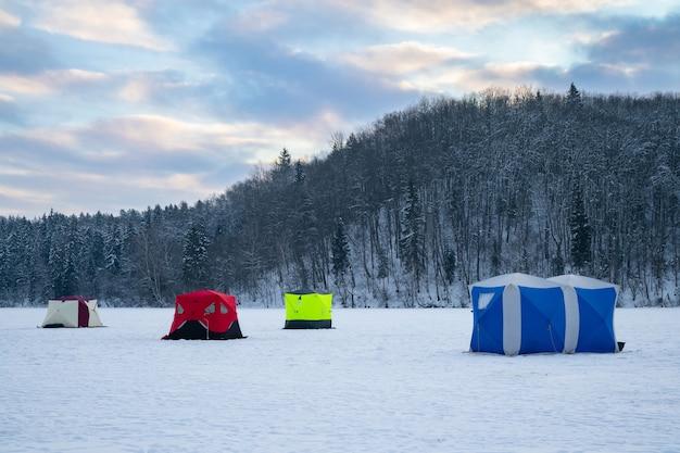 日没時の凍った湖の氷釣りテント
