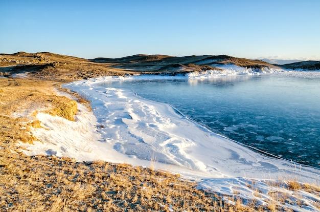 Льдины плавают по воде туман в озере байкал и холм. закат солнца