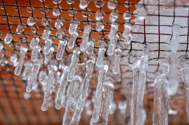 Ice on the grate formed after an icy rain with icicles after freezing rain