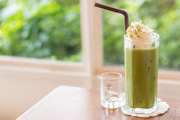 Ice green tea latte drink with whip cream topping on wooden table with nature bokeh