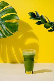 Ледяной зеленый чай матча здоровый напиток в жаркий летний день бежево-желтый фон