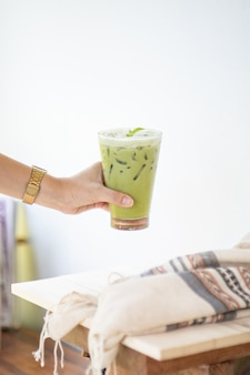 Ice green tea or matcha latte on tall glasses with straw on white wood table and clothes decoration object.
