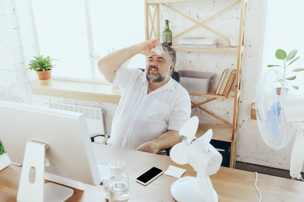Ice helping businessman manager in office with computer and fan cooling off feeling