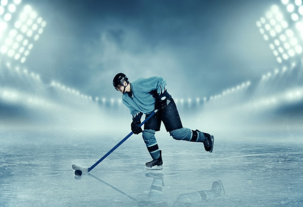 Ice hockey player in equipment poses on stadium