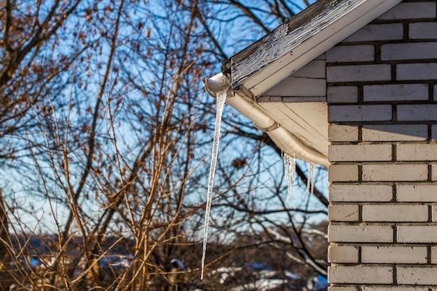 家の屋根の上の氷のつらら