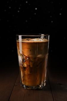 나무 테이블에 키 큰 유리에 아이스 라 떼 커피. 투명 유리에 우유와 블랙 커피. 실버 bokeh와 검은 배경.