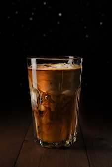 Ice latte coffee in tall glass on wooden table. black coffee with milk in transparent glass. black background with silver bokeh.