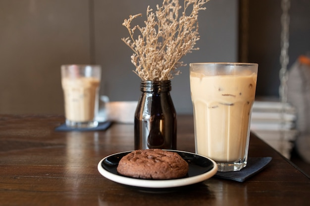 Ice latte coffeein a glass  with chocolate chip cookie on a wooden table