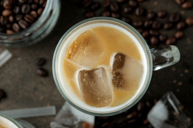 Ледяной латте или ледяной кофе с молоком и кубиками льда в стеклянном стакане на темном фоне. освежающий напиток. летний напиток. вид сверху