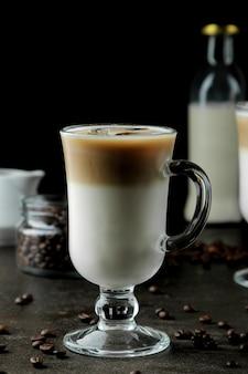 Ледяной латте или ледяной кофе с молоком и кубиками льда в стеклянном стакане на темном фоне. освежающий напиток. летний напиток.