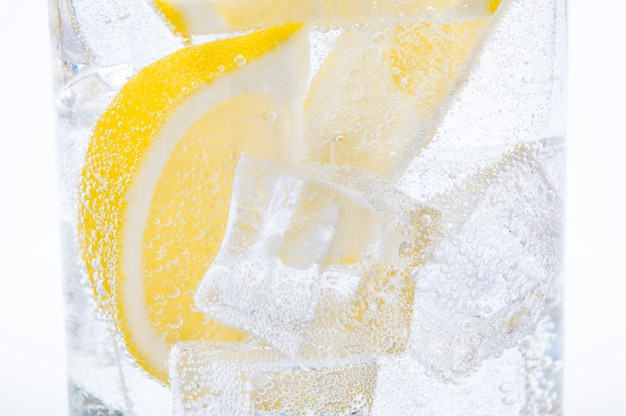 Ice, lemon slices and clear water in a glass.