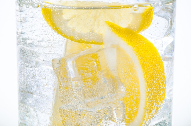 Ice, lemon slices and crystal clear water in a glass.