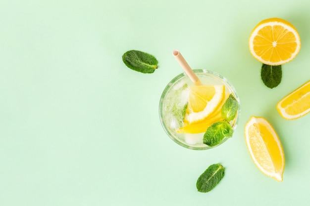 녹색 배경에 민트를 넣은 얼음 레몬 물이나 레모네이드. 무더운 여름을 위한 신선한 과일 음료 한 잔.