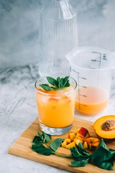 Ледяной лимонад в стакане с кусочками персика, свежей мятой и кубиками льда на столе