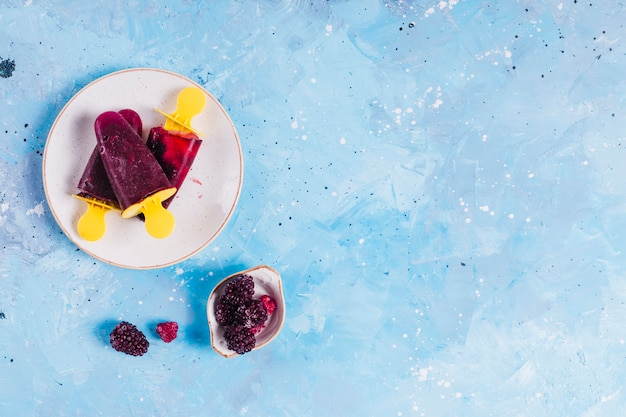 Ice lollies and berries on blue background