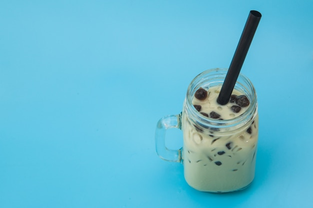 Ice milk tea wiht bubble boba in the glass jar on blue background