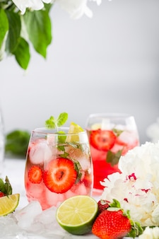 Ice pink lemonade with strawberries, lime, basil and mint