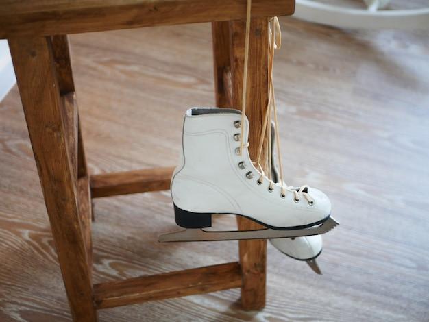 아이스 스케이트는 나무 의자에 매달려 있습니다. 고품질 사진