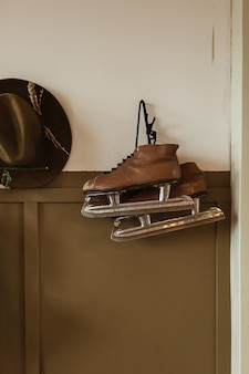 Ice skates and hat hang on the wall. hipster minimalist concept