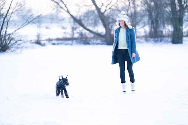 Ice skating on the ice of a frozen lake young attractive woman with dog