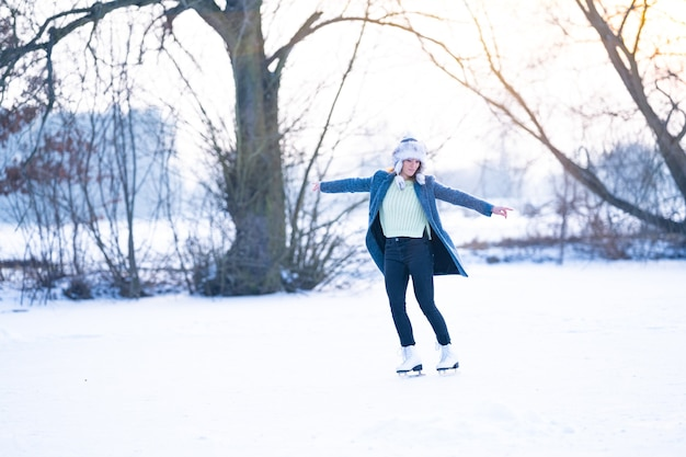 Ice skating on the ice of a frozen lake young attractive woman