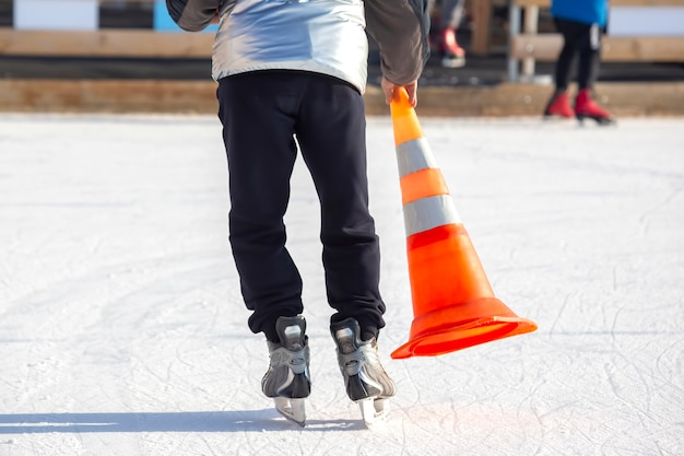 Ice skating man with cone plastic safety road sign in hand