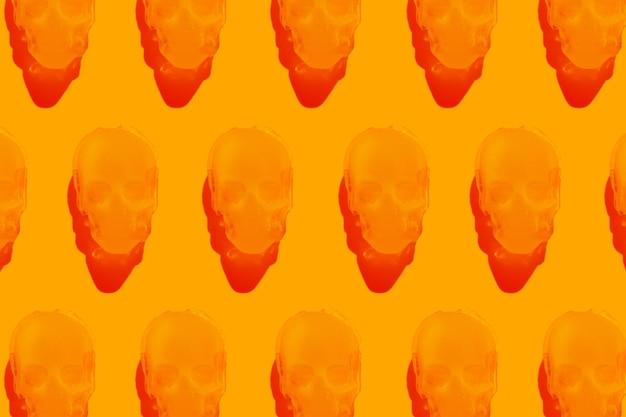 オレンジ色の背景の氷の頭蓋骨のパターンハロウィーンの楽しい不気味な背景