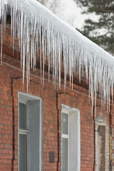 Ice stalactite hanging from the roof with red brick wall. winter season