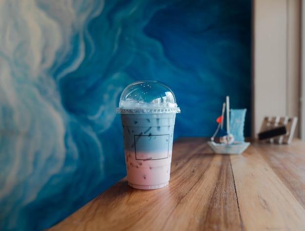 アイスストロベリーミルクとバタフライピーミルクを木製のテーブルにグラデーションで混ぜ、清涼飲料水。透明テイクアウトカップ。