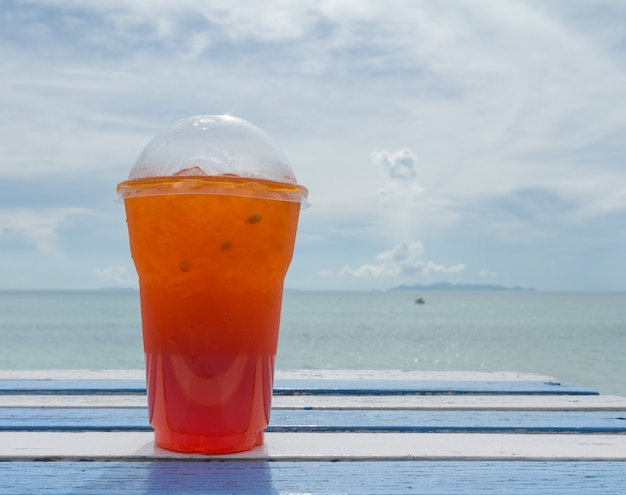 Чашка чая со льдом на белом столе на деревянный стол на пляже