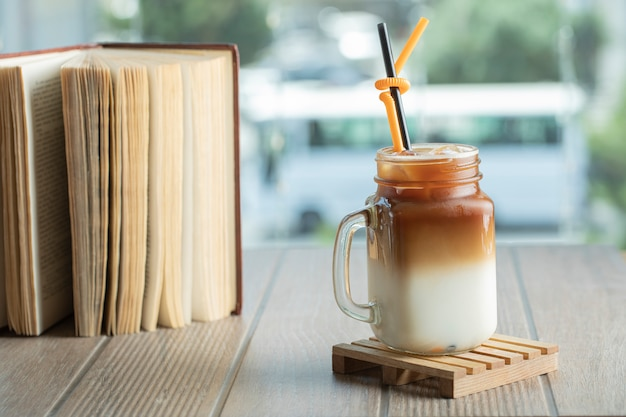 Ice tea with caramel sauce and milk in the jar on the table