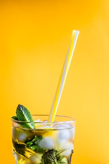 Ice tea with ice, lemon and mint on a combined colored yellow background